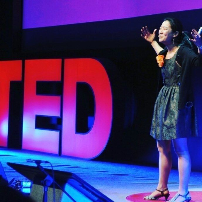Global Happiness Coach and WITH Warrior Kyla Mitsunaga speaking on the TED stage