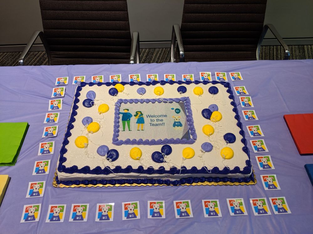 """Our """"Welcome To The Team"""" cake.  The little squares are stickers or our mascot """"Stuie"""" (my dog) we had made"""