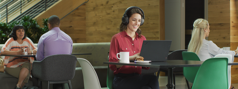 Person sitting in an open space environment wearing a Teams-certified headset while attending an online meeting