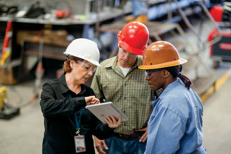 Factory employees using a Surface tablet