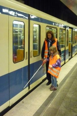 Training a young student to find the doors on the Munich subway, using a white cane.