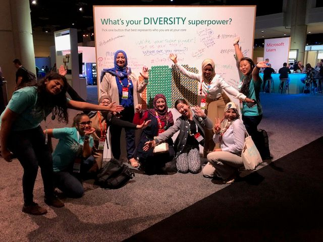 Happy attendees from around the world at the Diversity Superpower wall where people began writing inspiring quotes after all the buttons were gone!